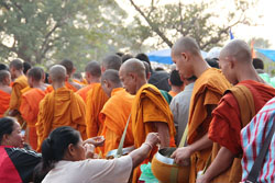 These people are giving donations to Buddhist monks in Laos. Altruism is very unusual in primates, but humans often act altruistically. Image by GuillaumeG.