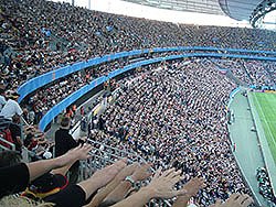 Spectators at a sporting event use human nature to make the wave. You stand up when those closest to you stand and lift your arms up. You sit down when they do. That helps to create the illusion of a wave ripple going around the stadium.